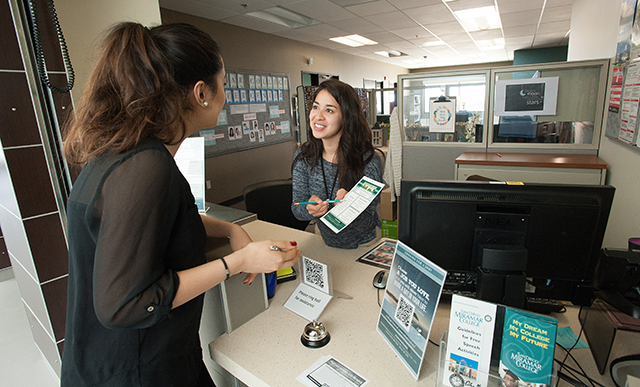 Image of Career Center representative giving information to a student at the front desk